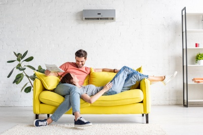 A man and a woman sitting on a couch together under an HVAC unit.