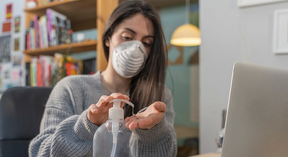 A woman with a mask on using hand sanitizer.