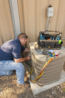 A technician working on an air conditioner unit.